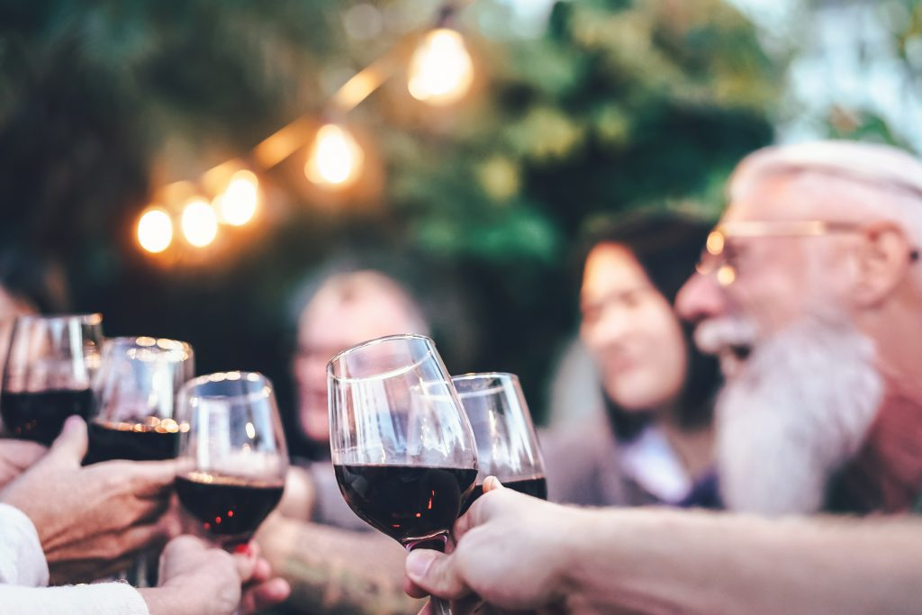 Happy family eating and drinking red wine at dinner barbecue party outdoor - Mature and young people cheering and toasting with wineglass on rooftop - Food, drink and weekend lifestyle activities
